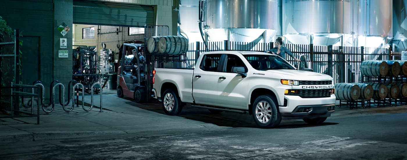 A white 2021 Chevy Silverado 1500 is shown from the side with barrels being loaded into the bed with a forklift.