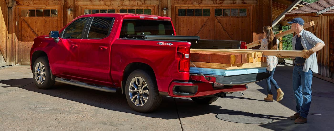 A red 2021 Chevy Silverado 1500 is shown with lumber being loaded into the bed.