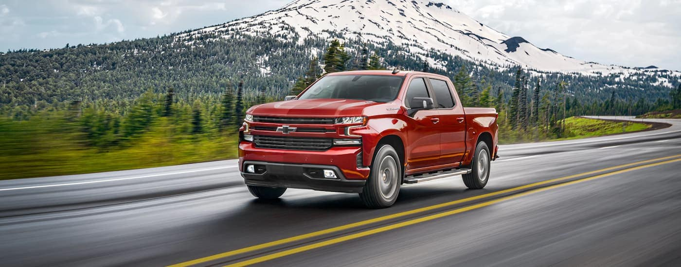A red 2021 Chevy Silverado is shown driving down the highway, with mountains in the background,  after the 2021 Chevy Silverado 1500 vs 2021 Ram 1500 comparison.