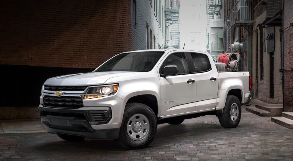 A popular Chevy commercial vehicle, a white 2021 Chevy Colorado, is shown angled left while parked in the city.