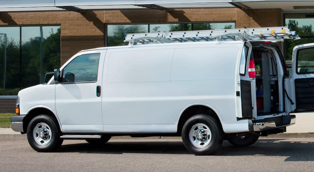 A white 2021 Chevy Express Van is shown from the side in front of a brick building, with a ladder on the roof and rear doors open.