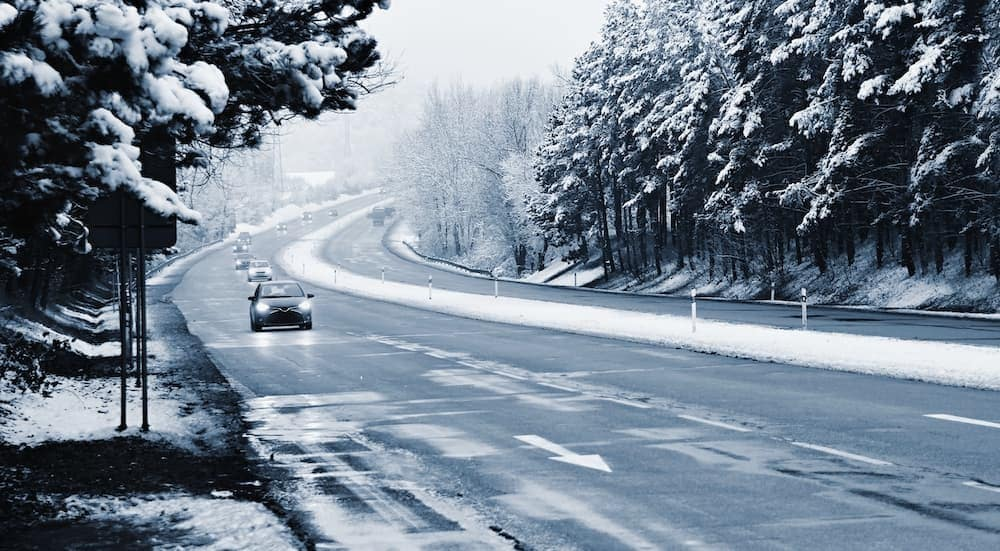 A snowy two lane highway is shown with cars commuting.