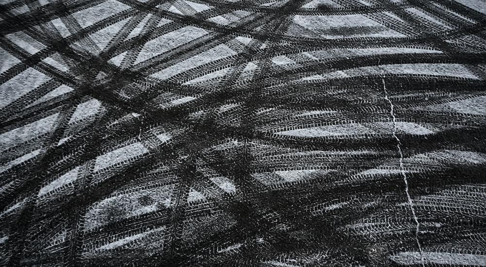 A close up is shown of snow covered pavement covered with criss crossing tire tracks.