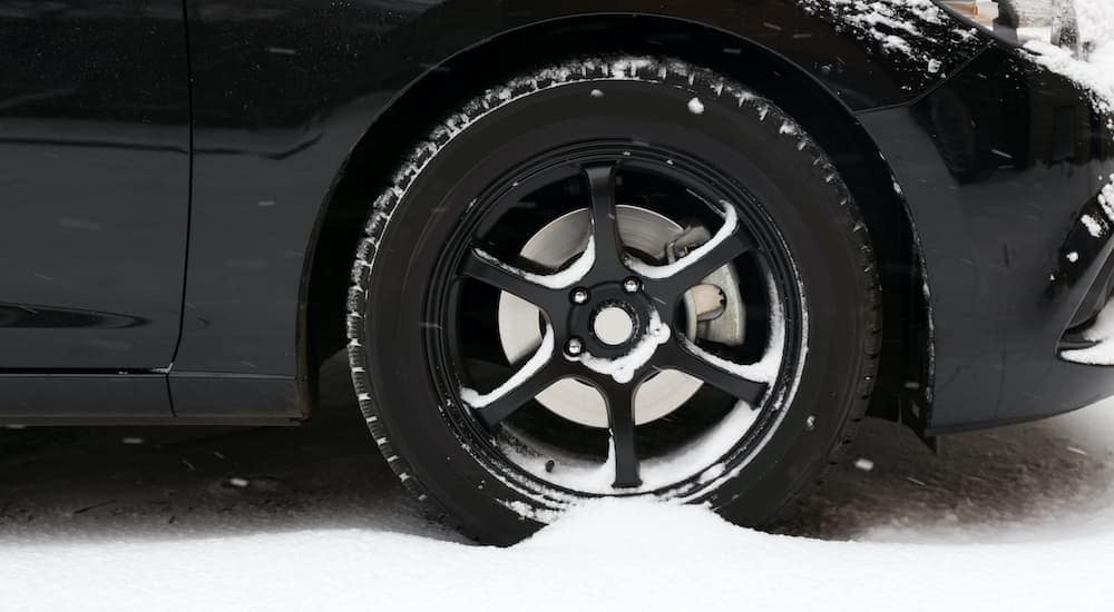 A close up is shown of a black wheel covered in snow, wrapped in Indianapolis winter tires.
