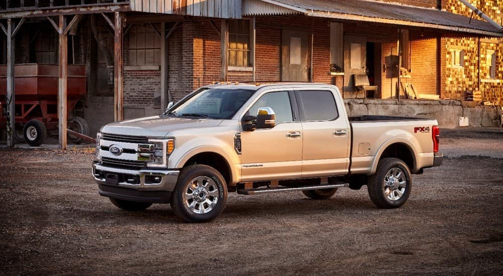 A popular used commercial vehicle for sale, a 2017 Ford F-350 King Ranch, is parked in front of a brick building.