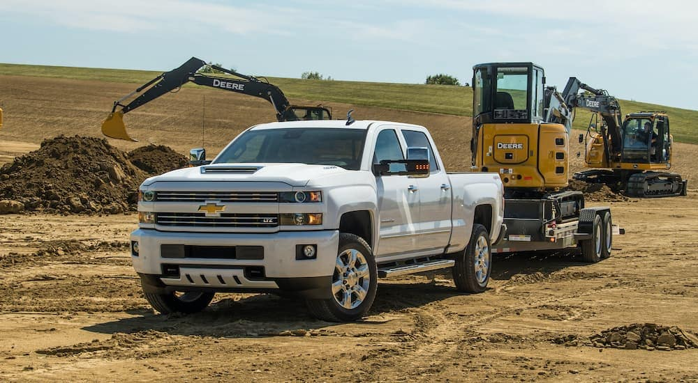 A white 2018 Chevy Silverado 2500HD is towing a front loader through a construction site.