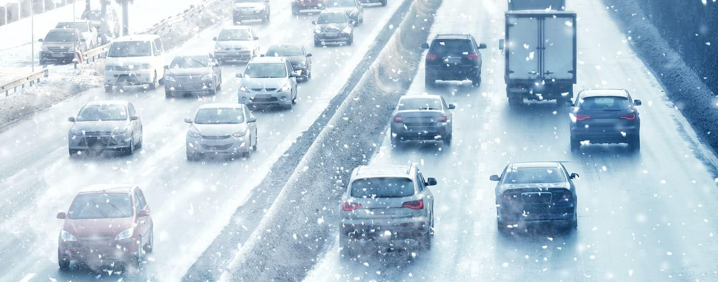A busy highway is shown with many vehicles driving in the snow.
