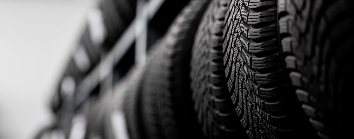 A black and white photo shows a close up of a rack of winter tires near me.