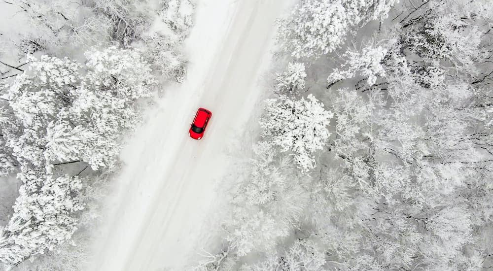 A red vehicle is shown from a high angle driving down an empty road, covered in snow.