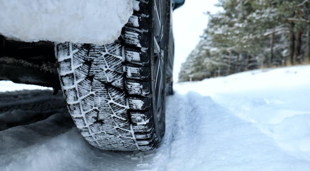 A popular set of winter tires near me are shown in close up driving through the snow.