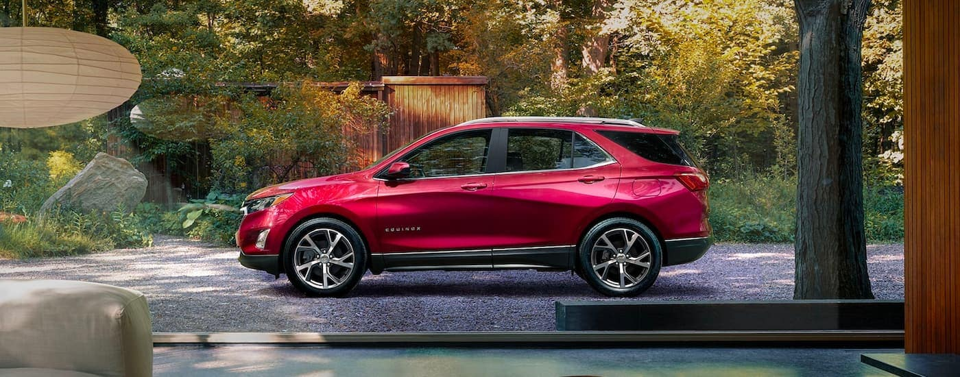 A red 2021 Chevy Equinox is shown from the side parked in a driveway with trees in the background.