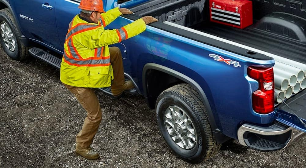 A close up shows a construction worker climbing on side of a blue 2021 Chevy Silverado 2500HD to get parts from the bed.