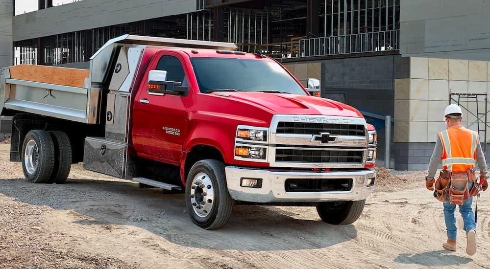 A construction worker is shown walking past a red 2021 Chevy Silverado 5500HD parked at a work site.