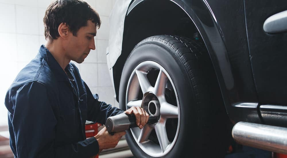 A close up shows a mechanic with an impact gun removing a tire at an Indianapolis tire shop.