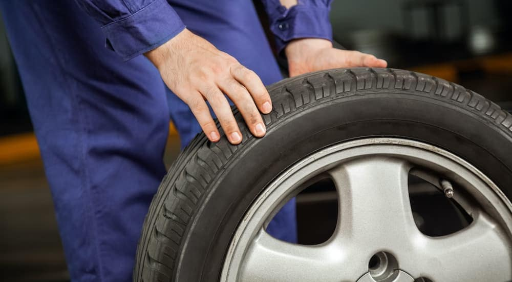 A close up shows a mechanic rolling a tire and rim.