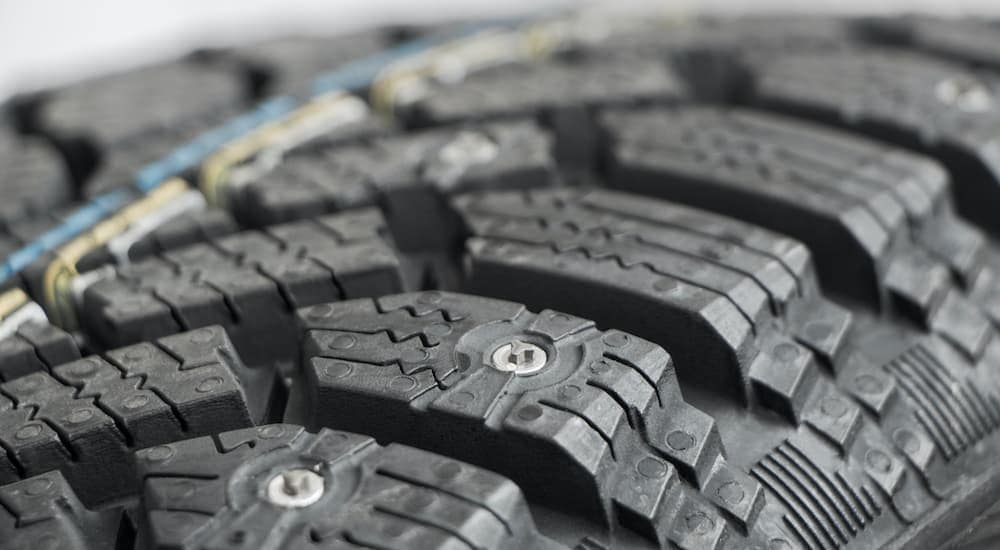 A close up shows the tread and studs on a studded snow tire.