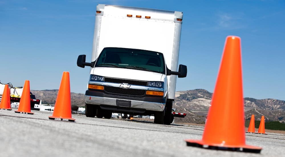 A white 2016 Chevy Express 4500 Cutaway is shown from a low angle surrounded by orange cones.