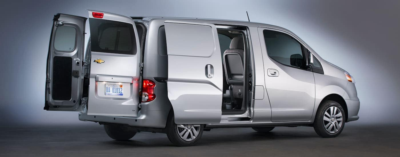 A silver 2017 Chevy City Express is shown from the side with its side and rear doors open.