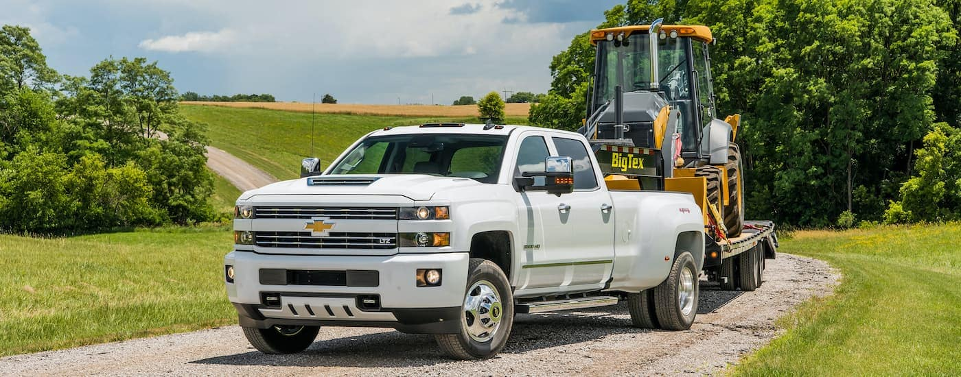 A popular used commercial vehicle for sale, a white 2018 Chevy Silverado 3500HD LTZ, is parked on a dirt path towing a front loader.