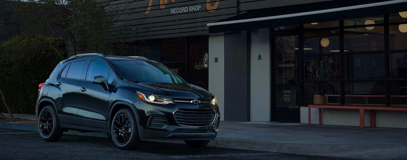 A black 2021 Chevy Trax is shown from the side while parked outside of a record shop at night 2021 Chevy Trax vs 2021 Ford EcoSport comparison.