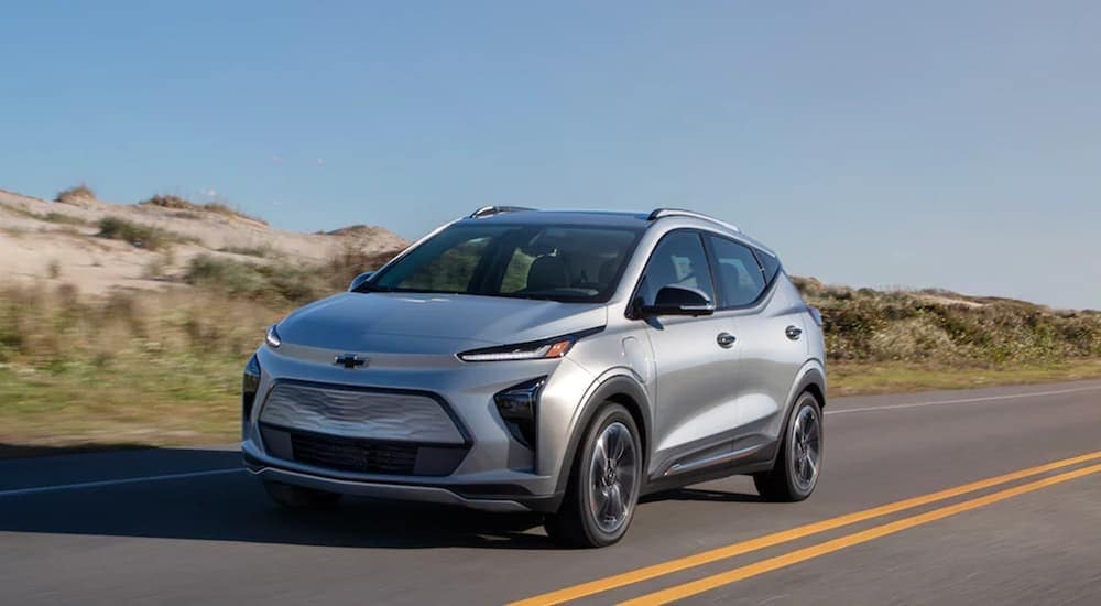 A silver 2022 Chevy Bolt EUV, a new Chevy EV, is driving past beach sand.