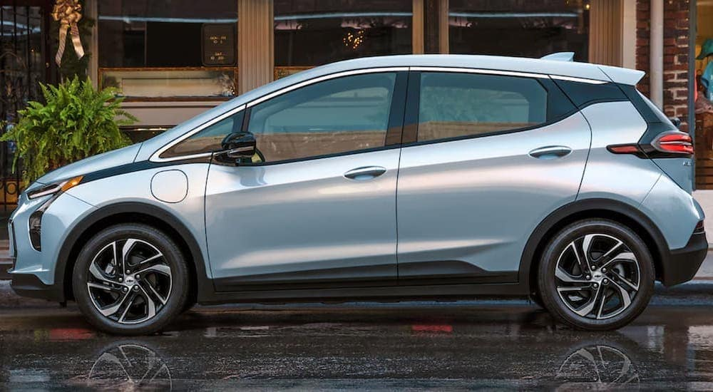 A light blue 2022 Chevy Bolt EV is shown from the side on a city street.