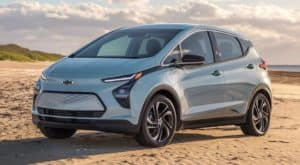 A light blue 2022 Chevy Bolt EV is parked on beach sand.