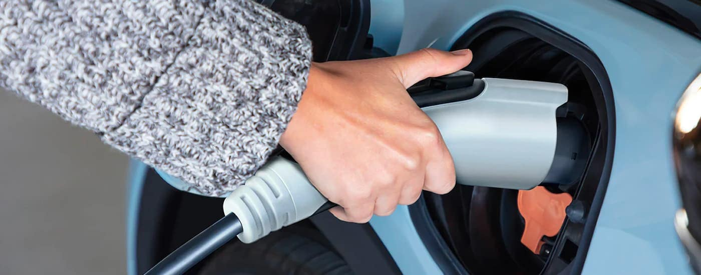 A close up shows a hand plugging a charger into a pale bue 2022 Chevy Bolt EV.