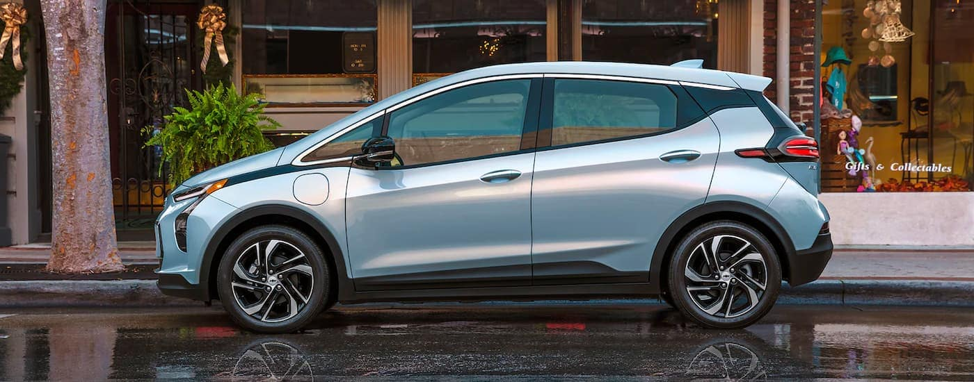 A pale blue 2022 Chevy Bolt EV is shown parked on a wet street in front of a collectible shop.