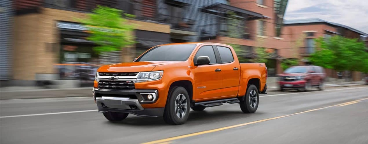 An orange 2021 Chevy Colorado Z71 is shown driving past blurred city buildings.