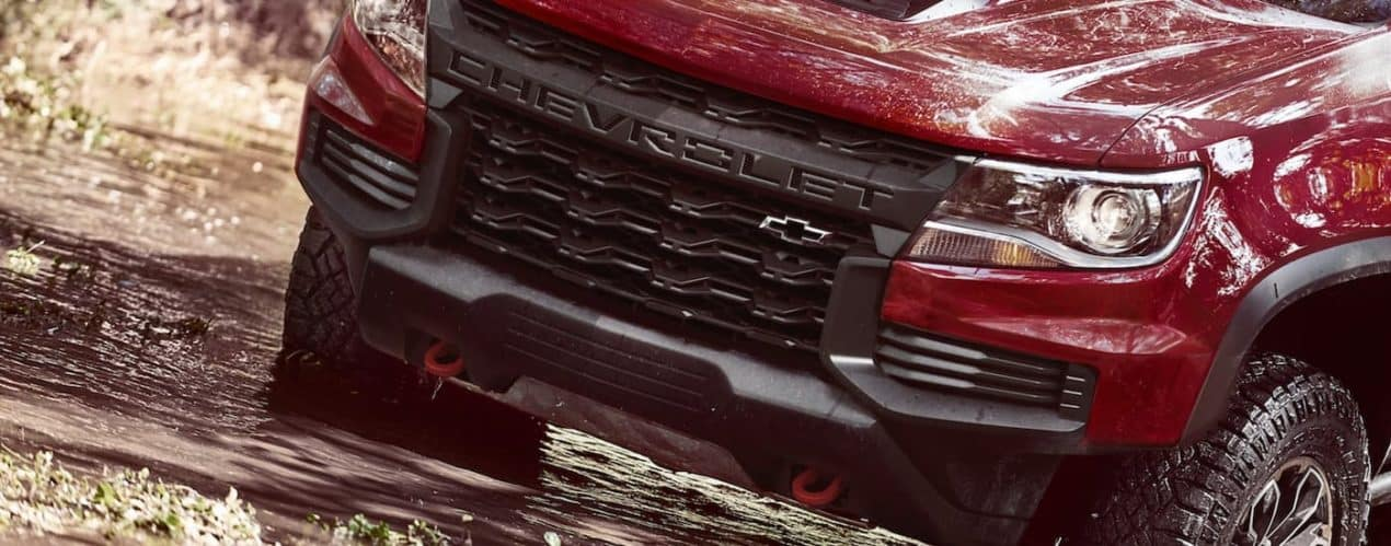 A close up shows a red 2021 Chevy Colorado ZR2 driving through a large mud puddle.