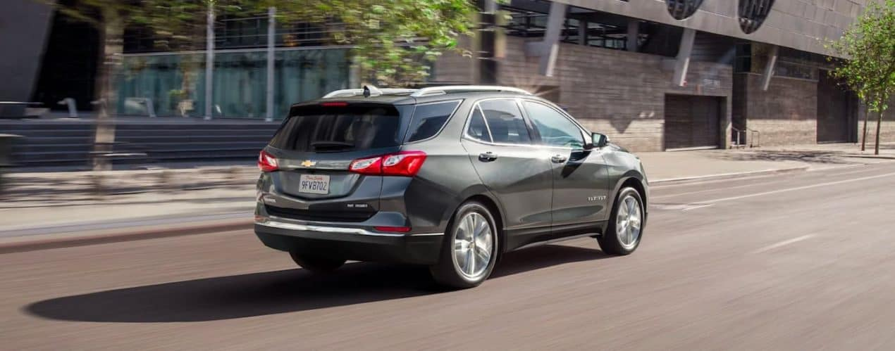 A grey 2021 Chevy Equinox is shown from the rear driving down a city street.