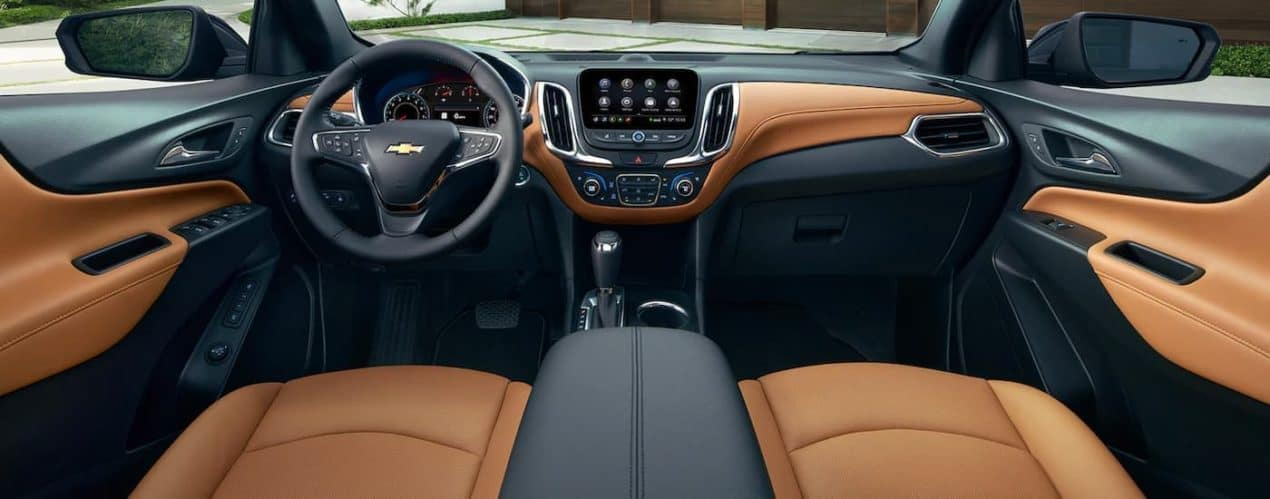 The brown and black front interior is shown from the rear seats in a 2021 Chevy Equinox.