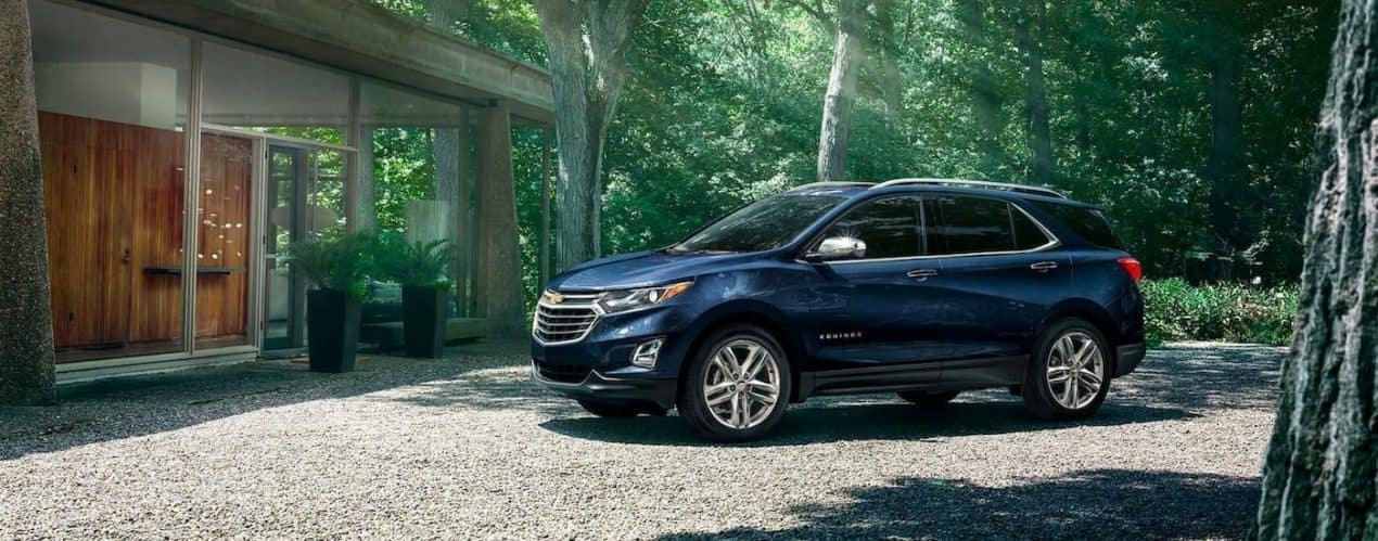 A blue 2021 Chevy Equinox is parked on a gravel driveway next to a modern house after winning the 2021 Chevy Equinox vs 2021 Honda CR-V comparison.