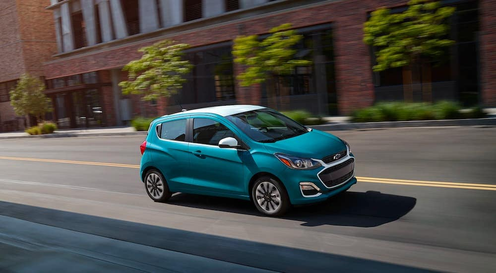 A teal 2021 Chevy Spark is shown driving through the city after leaving a Chevy dealership in Indianapolis.