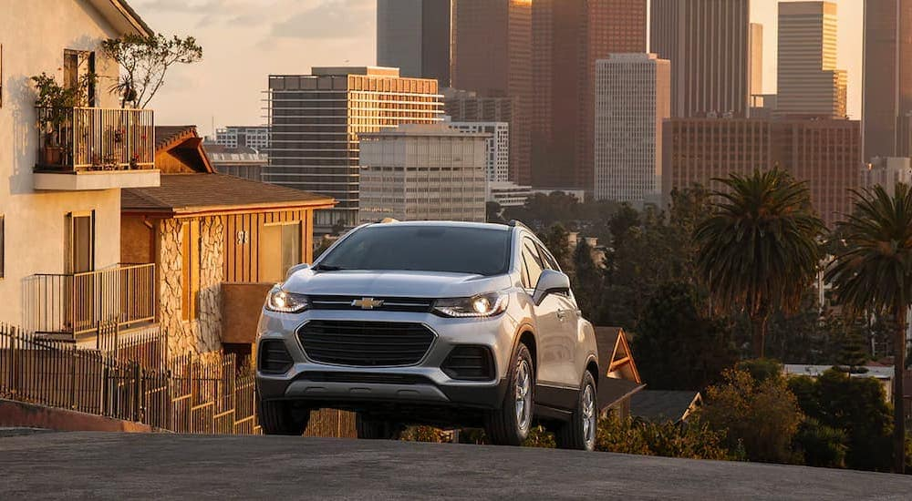 A silver 2021 Chevy Trax is shown from the front cresting a hill in the city.
