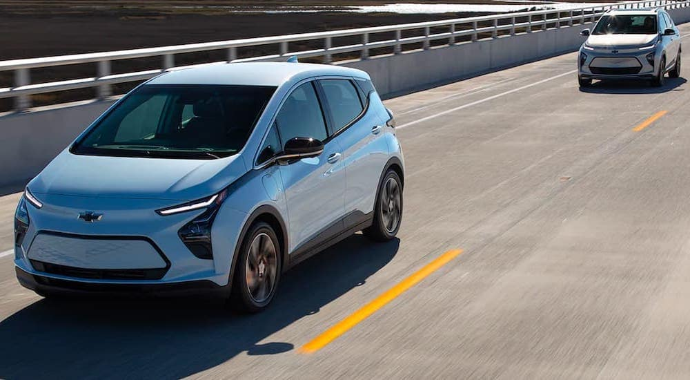 A pale blue 2022 Chevy Bolt EV and Bolt EUV are shown driving on the highway together.
