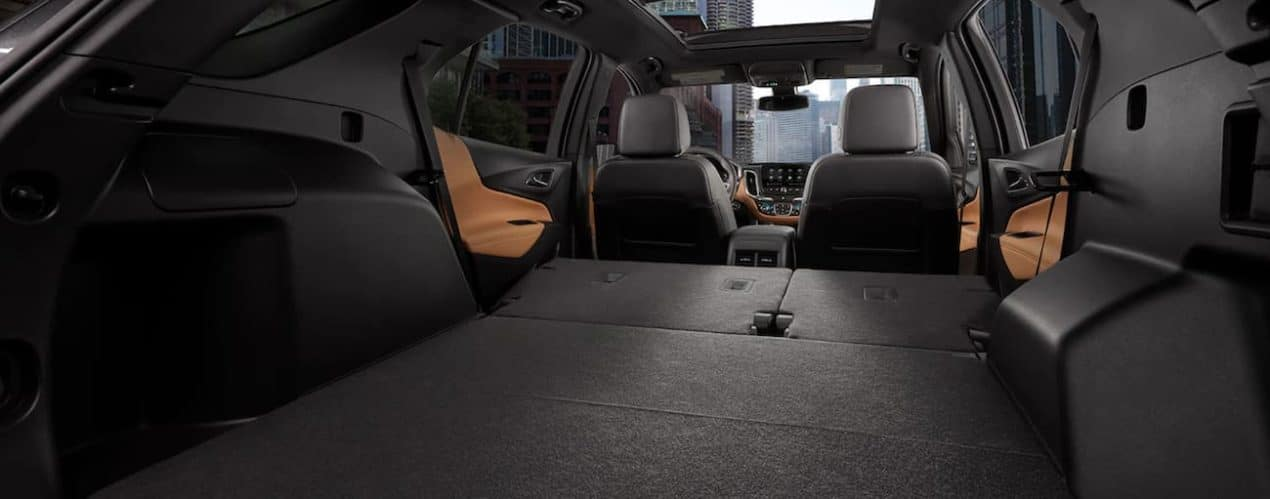 The cargo area of a 2021 Chevy Equinox is shwon with the rear seats folded down.