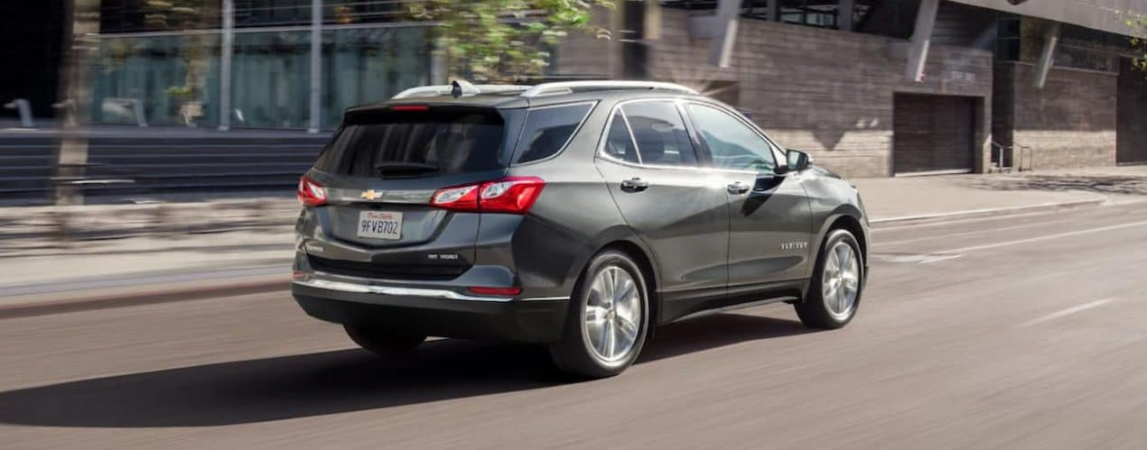 A grey 2021 Chevy Equinox is driving on a city street after winning the 2021 Chevy Equinox vs 2021 Toyota RAV4 comparison.