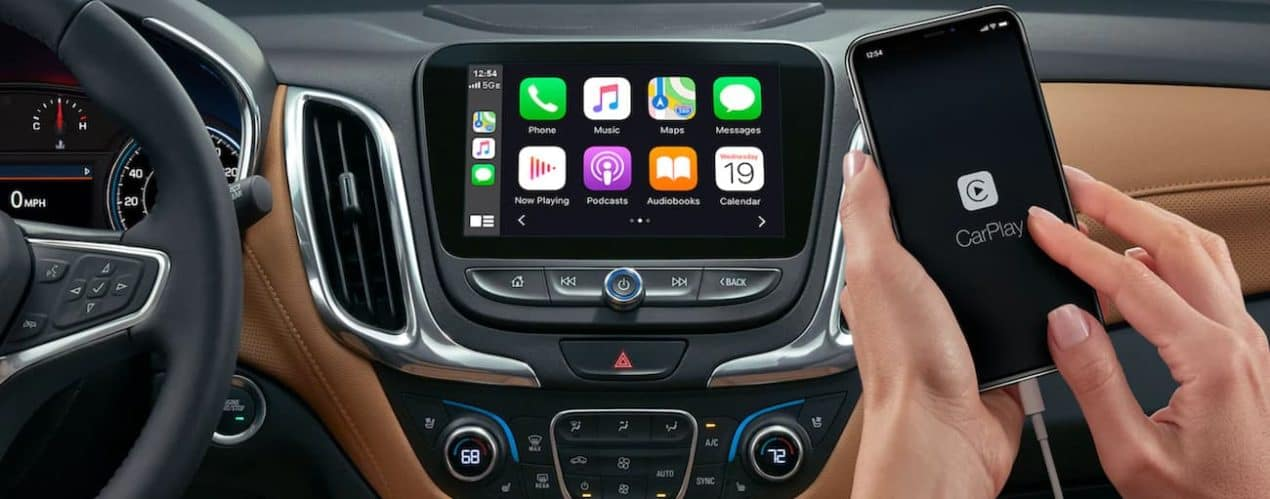 A phone with CarPlay on the screen is in front of the 2021 Chevy Equinox infotainment screen with app icons displayed.