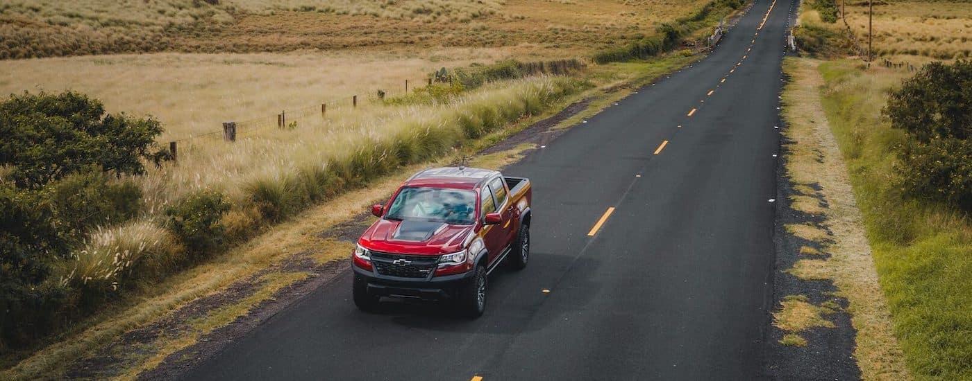 A red and black 2021 Chevy Colorado ZR2 is shown driving down an empty road after leaving a Chevy truck dealer in Indiana.