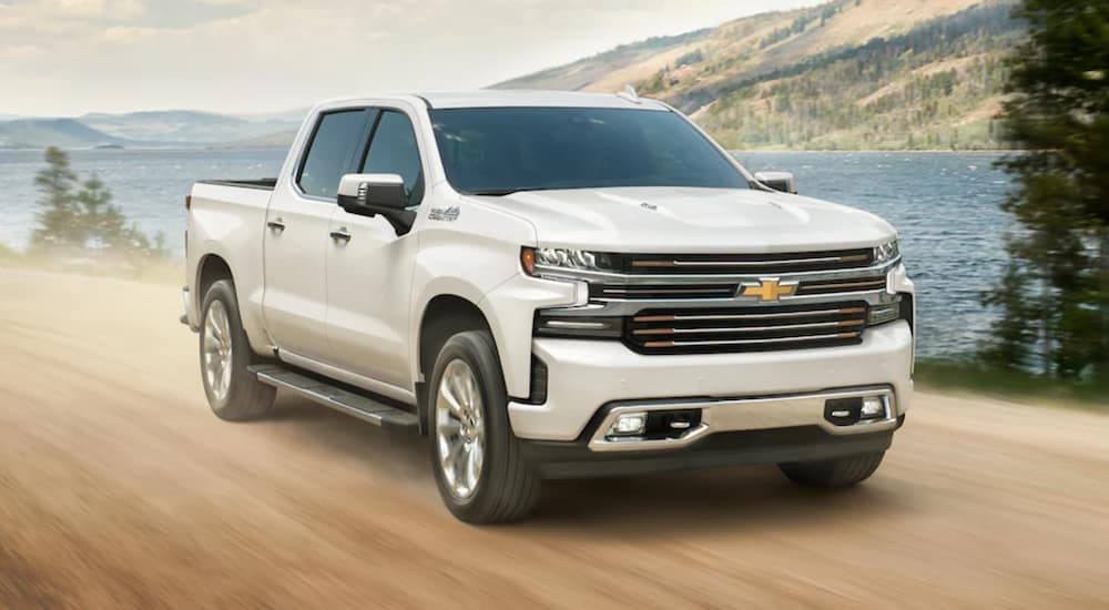 A white 2021 Chevy Silverado 1500 High Country is driving past a lake.