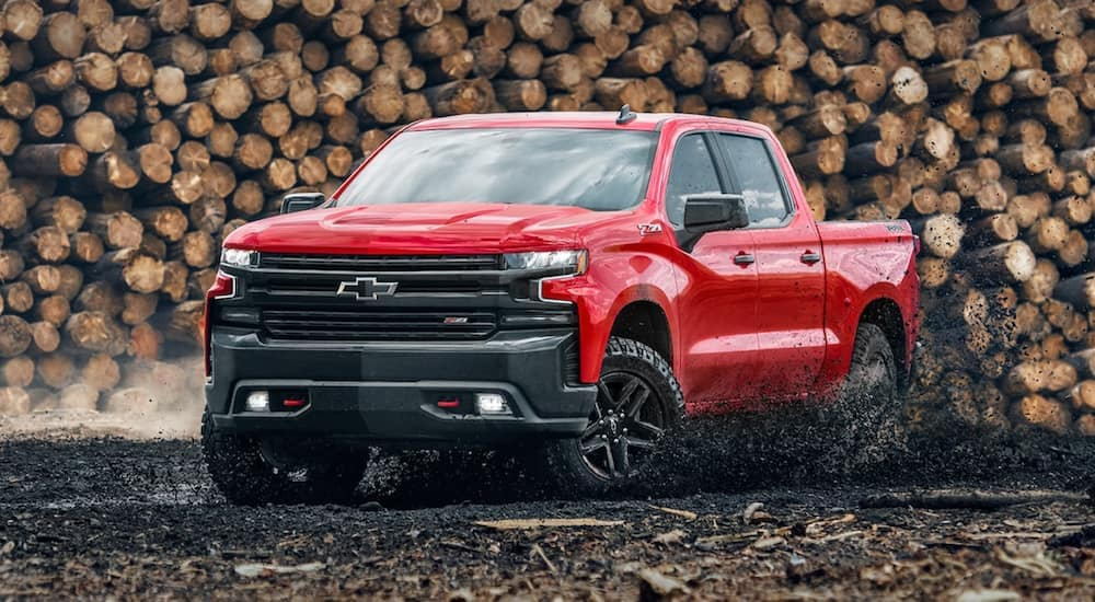 A 2021 Chevy Silverado 1500 LT Trail Boss is driving through mud in front of a log pile.