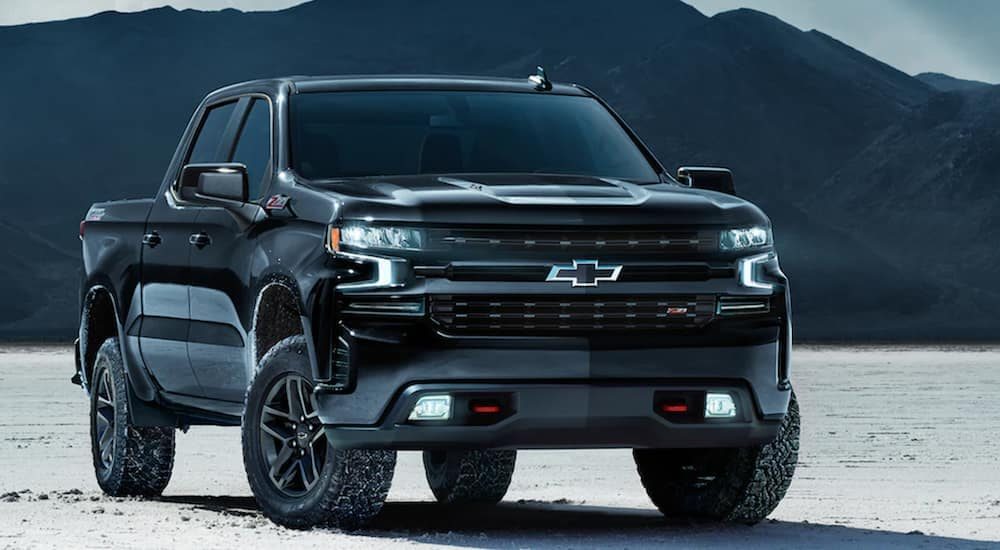 A black 2021 Chevy Silverado 1500 Midnight Edition is parked in a snow covered field after leaving a Chevy truck dealer in Indianapolis.