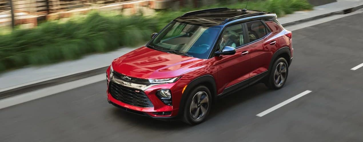 A red 2021 Chevy Trailblazer is driving on a multi-lane road past shrubs.