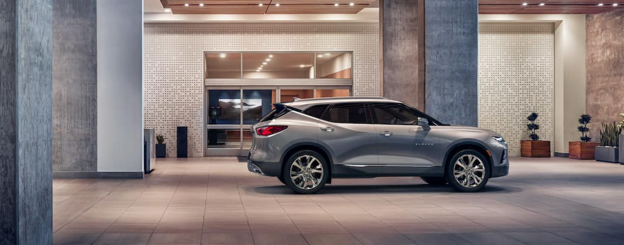 A silver 2022 Chevy Blazer is parked in front of a modern building.