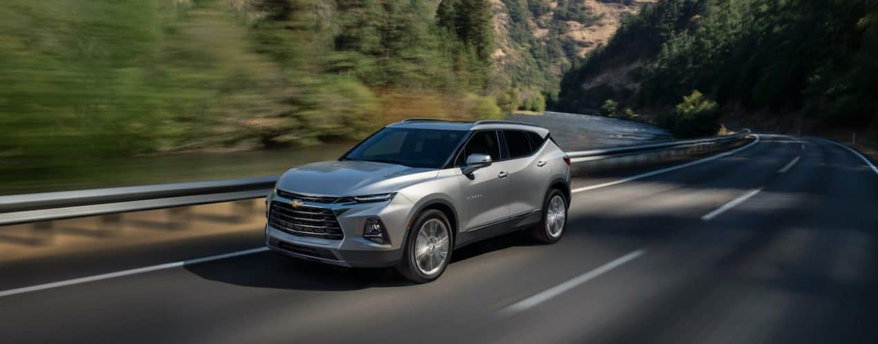 A silver 2022 Chevy Blazer is shown from the side driving down an open road.
