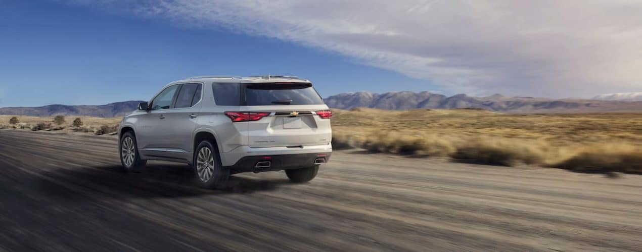 A white 2022 Chevy Traverse is shown from the rear driving on an open road.