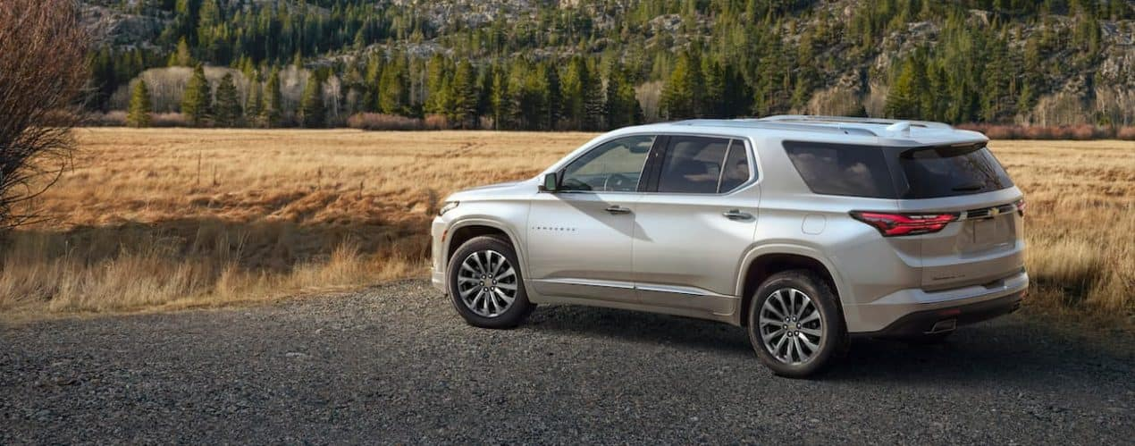 A white 2022 Chevy Traverse is shown parked in front of mountains.