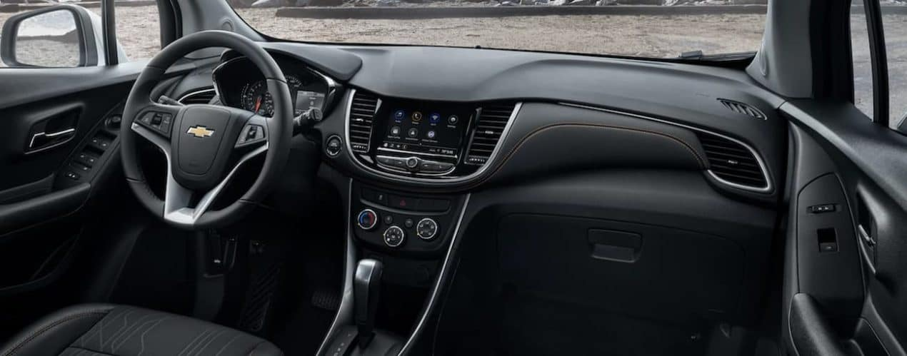 The black interior of a 2022 Chevy Trax shows the steering wheel and infotainment screen.
